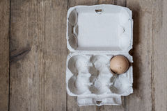 One egg in a carton. On an old wooden table Royalty Free Stock Photo