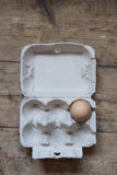 One egg in a carton. One organic egg in a carton on an old wooden table Stock Photography