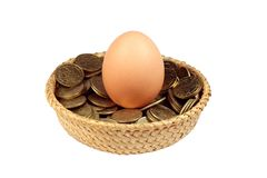 One egg and coins in a basket. A big egg with coins in a basket over white background isolated Royalty Free Stock Photos