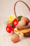 One egg near little basket with ribbons and flowers on wooden ta Stock Photo