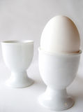 One egg - two egg cups. One white egg - two white egg cups Stock Photo