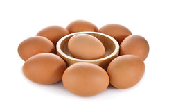 One egg in wooden bowl and others around on white background Stock Images