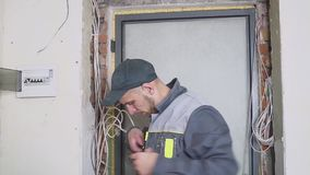 One electrician at work laying wiring cable with equipment and tools. Screwdriver. One electrician at work laying wiring cable stock footage