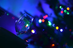 One empty askew wine glass and abstact night blury defocus bokeh light background photography. One empty askew wine glass and abstact night blury defocus bokeh Royalty Free Stock Photos