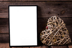 One empty  black frame and decorative heart with fairy light  on. Aged wooden background. Place for text. Mock-up for design Stock Images