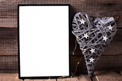 One empty  black frame and decorative heart with fairy light  on. Wooden background. Place for text. Mock-up for design Stock Images