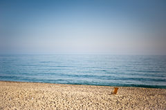 One empty chaise longue on the beach. One empty chaise longue on a sandy beach in a sunny day royalty free stock images