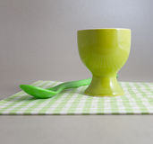 One empty green egg cup and spoon Stock Photos