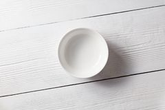 One empty plate on a white wooden kitchen table. Top view Stock Photos