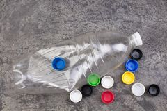 One empty used plastic bottles, many plastic covers on bitonny, gray background. stock photo