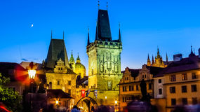 One end of the Charles Bridge with one of the statues and the tower at the entrance or the exit, Praha Prague. Czech Republic. Saint Vitus cathedral with part of Stock Image