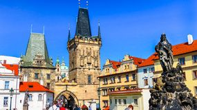 One end of the Charles Bridge with one of the statues and the tower at the entrance or the exit, Praha Prague. Czech Republic. Saint Vitus cathedral with part of Royalty Free Stock Image