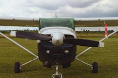 The one engine plane stands on the green grass in a cloudy day. Front view of plain. A small private airfield in Zhytomyr, Ukraine stock photography