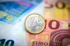 One Euro Coin on banknotes. Macro Stock Photo