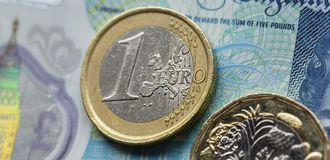 One Euro Coin on a British Five Pound Note in a Panoramic Format Stock Image