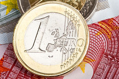 One Euro coin over banknotes Royalty Free Stock Photo