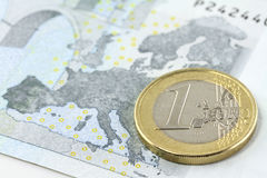 One euro coin over Europe map. On five euro note Stock Photo