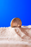 One Euro Coin. In sand against blue background Royalty Free Stock Image