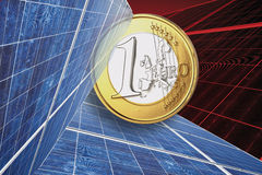 One euro coin and solar panel against red background, close up. Royalty Free Stock Image