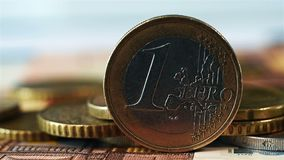 One euro coin. On stack of many euro coins and banknote stock video footage