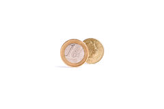 One Euro coin stand in front of the one Pound coin on white back Stock Image