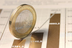 The One EURO coin standing on diagram. The macro of the one EURO coin standing on rising diagram Royalty Free Stock Photos
