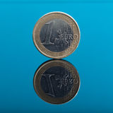 One Euro money coin on blue with reflection Royalty Free Stock Photography
