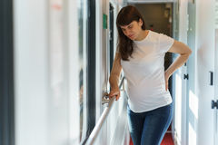 One european pregnant woman in t-shirt is getting back pain while traveling by railway Stock Photography