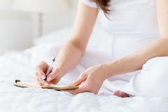 One european pregnant woman writes some idea or thouths in note book by pen sitting on white bed of light room at sunny Royalty Free Stock Photo