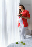 One european pregnant woman is writing and thinking some idea in notebook by pen in white bedroom at day time Royalty Free Stock Photos