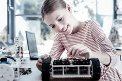 Beautiful girl smiling while constructing robotic vehicle. This one is even better than my previous. Smart young lady sitting at a table and enjoying the process stock image