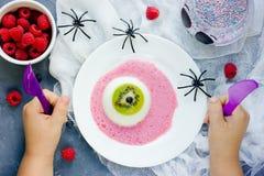 One eye panna cotta with kiwi and raspberry sauce, Halloween rec Royalty Free Stock Image