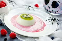 One eye panna cotta with kiwi and raspberry sauce, Halloween rec. Ipe. Creative idea for kids dessert on holiday party selective focus Royalty Free Stock Image