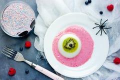 One eye panna cotta with kiwi and raspberry sauce, Halloween rec Stock Image