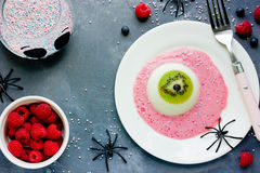 One eye panna cotta with kiwi and raspberry sauce, Halloween rec. Ipe. Creative idea for kids dessert on holiday party top view Royalty Free Stock Photos