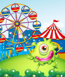 A one-eyed green monster at the carnival in the hilltop. Illustration of a one-eyed green monster at the carnival in the hilltop Royalty Free Stock Images