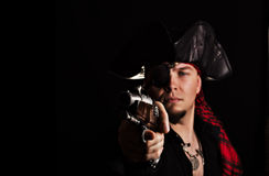 One-eyed young pirate aims a pistol old Royalty Free Stock Photos