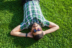 One fashion middle eastern man with beard, fashion hair style is resting on beautiful green grass day time. Royalty Free Stock Photography