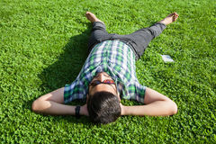One fashion middle eastern man with beard, fashion hair style is resting on beautiful green grass day time. Royalty Free Stock Images