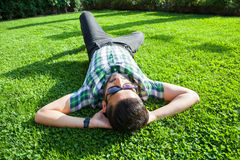 One fashion middle eastern man with beard, fashion hair style is resting on beautiful green grass day time. Royalty Free Stock Image