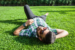 One fashion middle eastern man with beard, fashion hair style is resting on beautiful green grass day time. Stock Photography