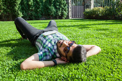 One fashion middle eastern man with beard, fashion hair style is resting on beautiful green grass day time. Stock Photo