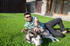 One fashion middle eastern man with beard and fashion hair style is resting and enjoy on beautiful green grass . Stock Image