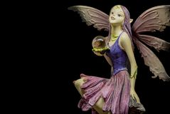 One female elf figurine in black background. One female elf figurine holding crystal ball reading tthe future Royalty Free Stock Images