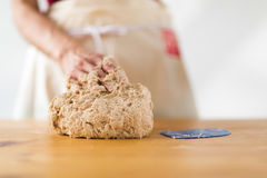 One female hand kneading dough on a wooden table Stock Photo