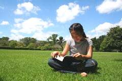 One fine day. Young teen reading in the park Royalty Free Stock Photo