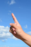 One finger of human hand on blue sky. Background Royalty Free Stock Photo