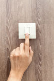 One finger switching turned on off, press the button. Wood wall background Stock Images