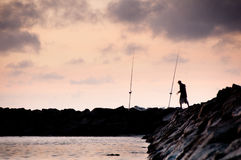 One fisherman on a breakwater at dawn Royalty Free Stock Image