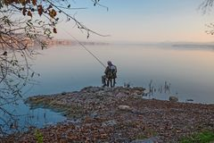 One fishermen, immersed in the quiet waters. Of a lake, are dedicated to sport fishing on a quiet summer afternoon Royalty Free Stock Image